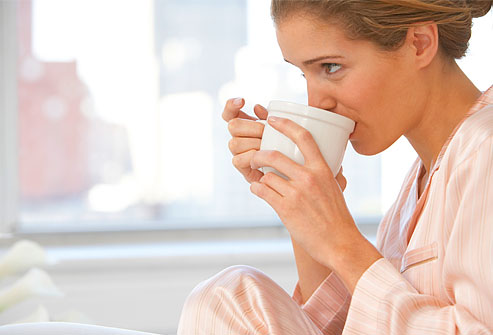 getty_rf_photo_of_woman_in_pajamas_drinking_coffee